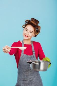 Молодая домохозяйка дает вам половник попробовать домашний суп