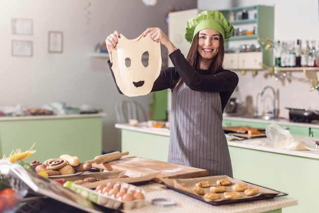 Young housewife having fun holding funny dough face while baking pastry in the kitchen