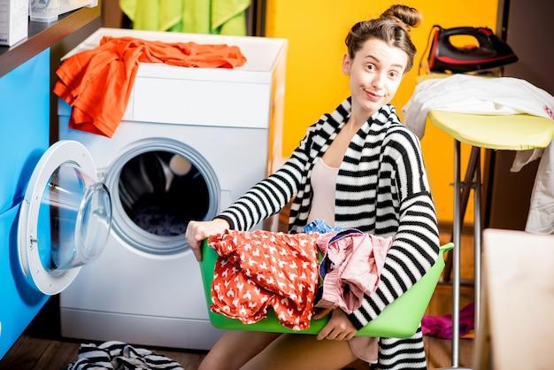 Молодая домохозяйка держит корзину с одеждой возле стиральной машины, сидя на полу дома