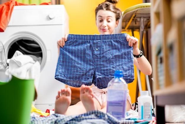 自宅でカラフルな服を着て洗濯機の近くに座っているズボンを保持している若い主婦
