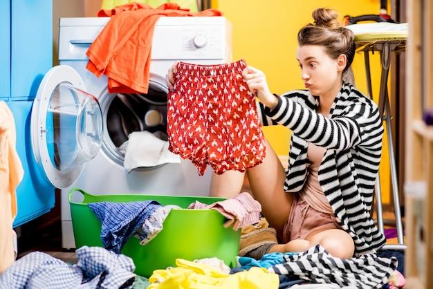 Молодая домохозяйка держит штаны, сидя возле стиральной машины с яркой одеждой дома