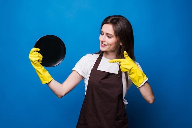 Молодая домохозяйка в перчатках показывает губку и чистую тарелку изолированы