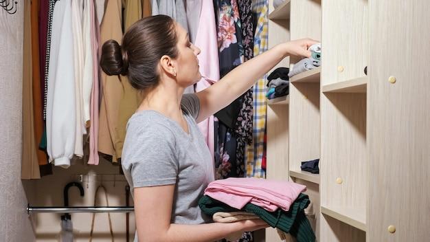Молодая домохозяйка в серой футболке кладет сложенную чистую одежду на разные деревянные полки в современной легкой гардеробной дома крупным планом