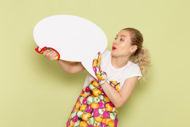 Молодая домохозяйка в рубашке и цветной накидке держит белый знак на зеленом