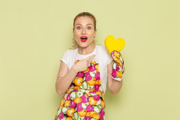 셔츠와 녹색에 노란색 심장 모양을 잡고 컬러 케이프 젊은 주부