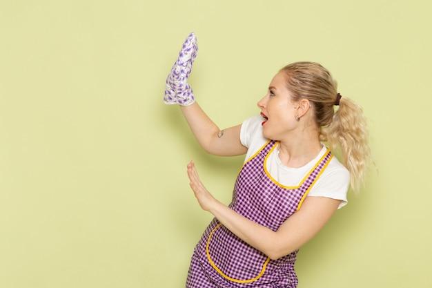 Молодая домохозяйка в рубашке и цветной накидке осторожно позирует на зеленом
