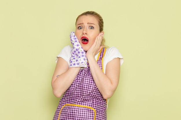 Молодая домохозяйка в рубашке и фиолетовой накидке в кулинарных перчатках с шокированным выражением лица на зеленом