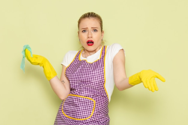 Молодая домохозяйка в рубашке и фиолетовой накидке с желтыми перчатками держит зеленую тряпку в замешательстве на зеленом