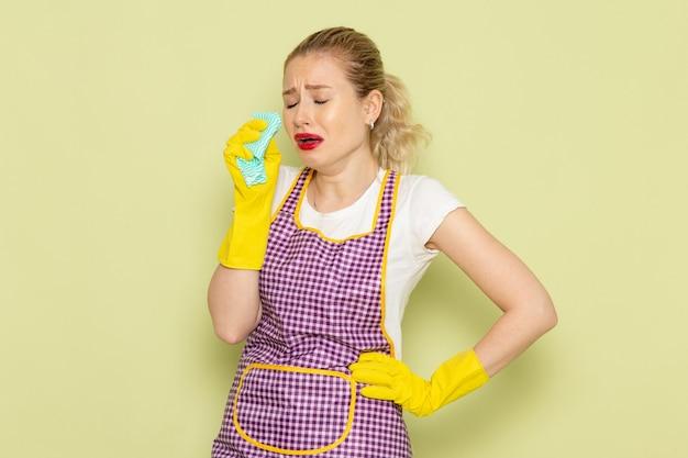Молодая домохозяйка в рубашке и фиолетовой накидке с желтыми перчатками держит зеленую тряпку и плачет на зеленом
