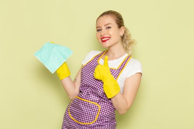 Молодая домохозяйка в рубашке и фиолетовой накидке с желтыми перчатками держит зеленую тряпку на зеленом