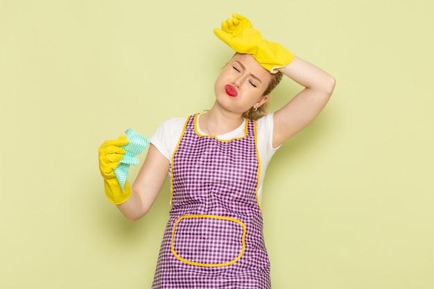 Молодая домохозяйка в рубашке и фиолетовой накидке с желтыми перчатками держит зеленый