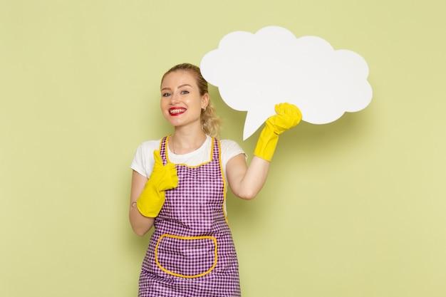 Молодая домохозяйка в рубашке и фиолетовой накидке с желтыми перчатками держит белый знак на зеленом