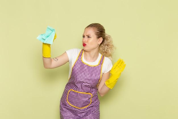 Молодая домохозяйка в рубашке и фиолетовой накидке с желтыми перчатками пахнет что-то на зеленом
