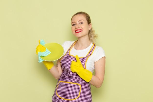 Молодая домохозяйка в рубашке и фиолетовой накидке желтые перчатки сушит тарелку на зеленом