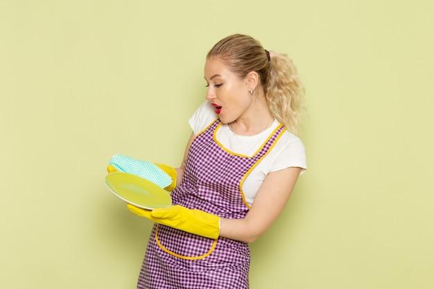 Молодая домохозяйка в рубашке и фиолетовой накидке желтых перчатках сушит тарелки на зеленом столе