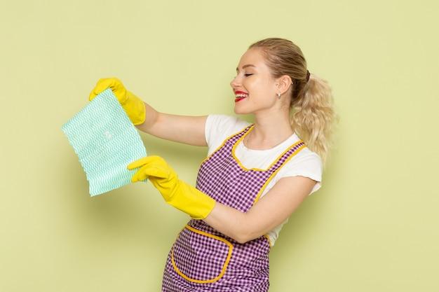 Молодая домохозяйка в рубашке и фиолетовой накидке в желтых перчатках позирует с довольным лицом на зеленом