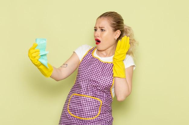 Молодая домохозяйка в рубашке и фиолетовой накидке желтых перчатках позирует с недовольным выражением лица на зеленом