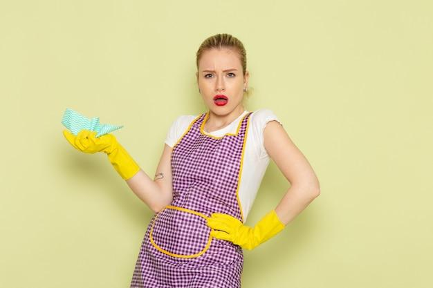 Молодая домохозяйка в рубашке и фиолетовой накидке в желтых перчатках позирует с недовольным лицом на зеленом