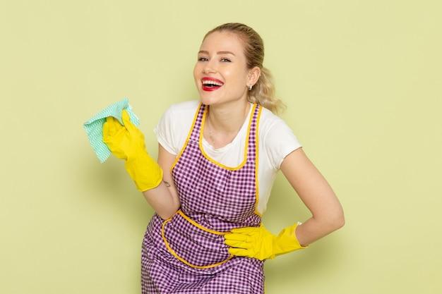 Молодая домохозяйка в рубашке и фиолетовой накидке с желтыми перчатками позирует с улыбающимся выражением лица на зеленом