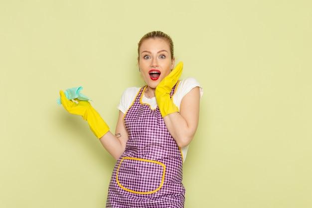 Молодая домохозяйка в рубашке и фиолетовой накидке в желтых перчатках позирует с удивленным выражением лица на зеленом