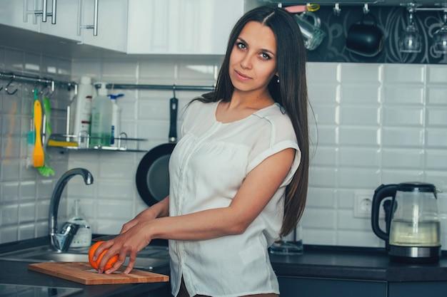 Молодая хозяйка на кухне, чтобы разрезать апельсин на доске