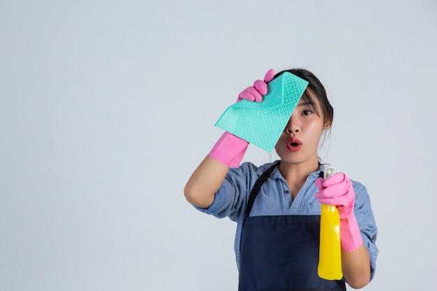 Молодая домохозяйка носит желтые перчатки во время уборки с продуктом чистой на белой стене.