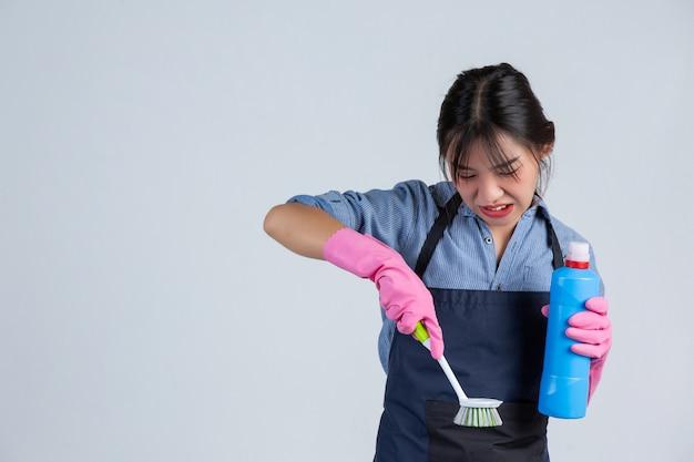 흰 벽에 깨끗 한 제품으로 청소하는 동안 젊은 주부 노란색 장갑을 끼고있다.
