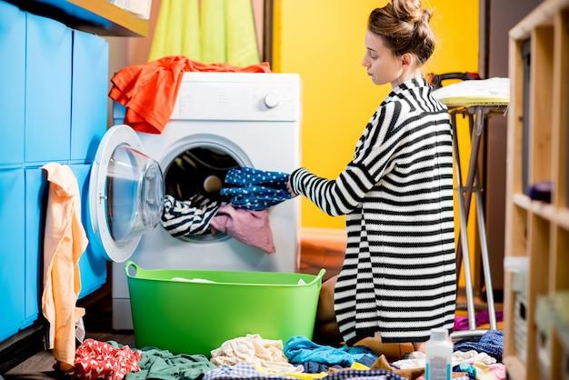 Молодая домохозяйка загружает одежду в стиральную машину, сидя на полу дома