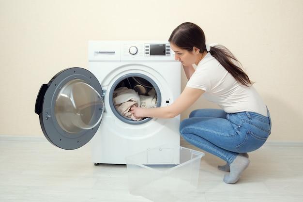 젊은 주부는 베이지색 벽 근처의 플라스틱 상자에서 더러운 옷을 현대 세탁기에 넣습니다