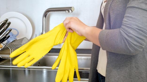 家事をする前に黄色いゴム手袋で手を保護する若い主婦。