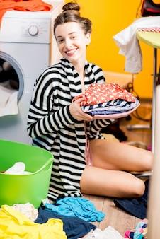 Молодая домохозяйка собирает одежду, сидя возле стиральной машины с яркой одеждой дома