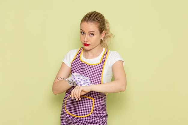 Giovane casalinga in camicia e mantello colorato che tiene i guanti da cuoco che indicano nel suo polso sul verde