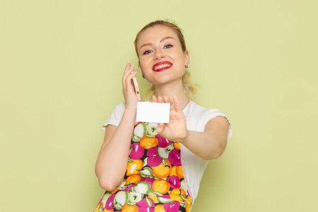 Giovane casalinga in camicia e mantello colorato che tiene telefono e carta sul verde