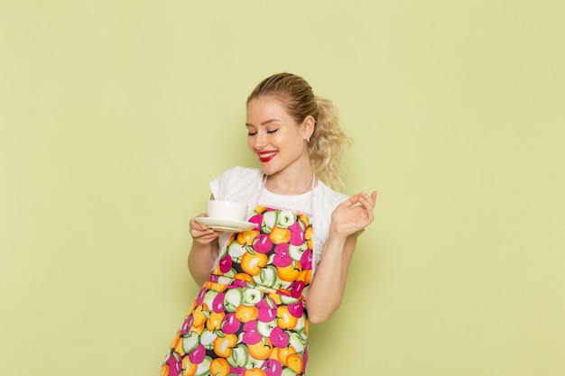 Giovane casalinga in camicia e mantello colorato che tiene tazza bianca sul verde