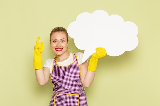 Giovane casalinga in camicia e mantello colorato con cartello bianco sorridente che indossa guanti gialli sul verde