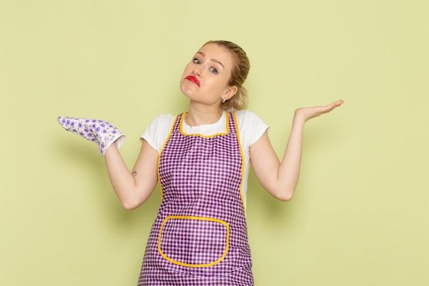 Giovane casalinga in camicia e mantello colorato solo in piedi e in posa sul verde
