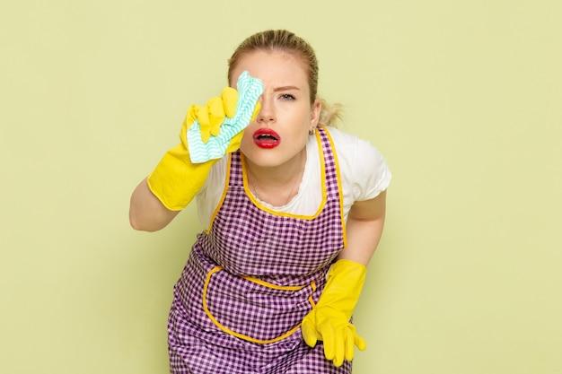 Giovane casalinga in camicia e guanti gialli mantello colorato pulizia sul verde