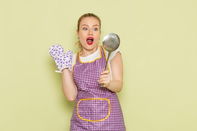 Giovane casalinga in camicia e mantello viola che tiene un cucchiaio d'argento sul verde