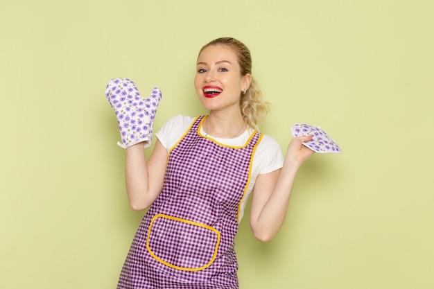 Giovane casalinga in camicia e mantello viola indossando guanti da cucina sul verde