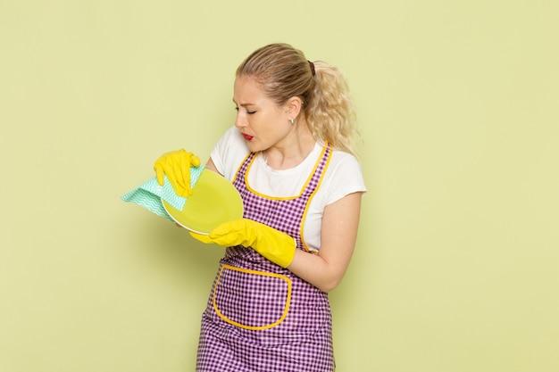 Giovane casalinga in camicia e guanti gialli mantello viola piatto di essiccazione sul verde