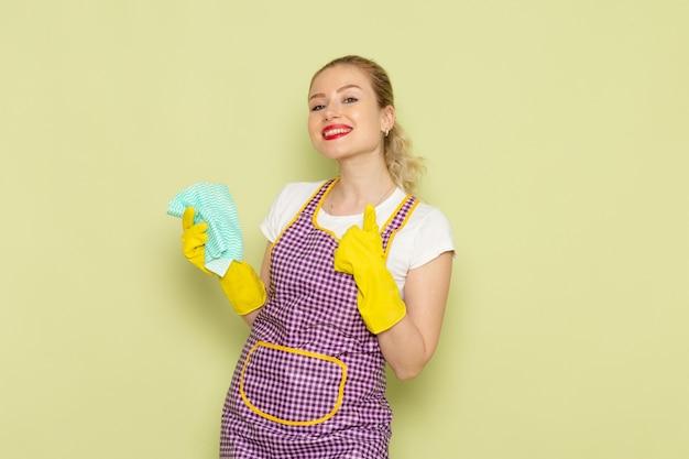 Giovane casalinga in camicia e guanti gialli mantello viola sorridente e in posa sul verde
