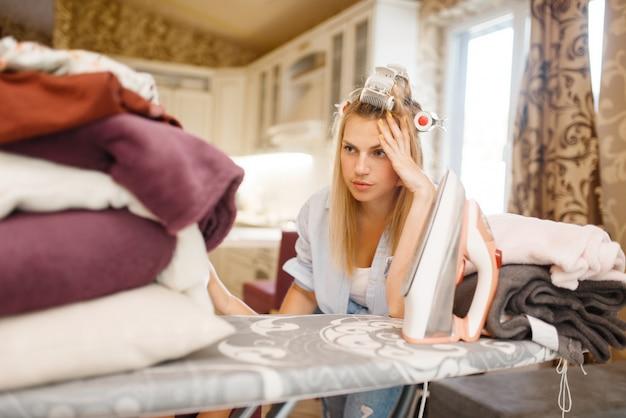アイロン台に座っている若い主婦。家で家事をして疲れている女性。家の中で女性が服にアイロンをかける