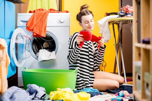 Молодая домохозяйка сидит возле стиральной машины с яркой одеждой дома