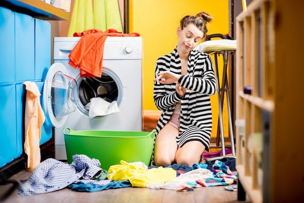 Молодая домохозяйка грустно сидит возле стиральной машины с большим количеством разноцветной одежды на полу дома