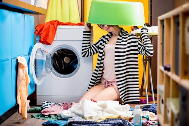 Молодая домохозяйка сидит с корзиной для одежды возле стиральной машины дома