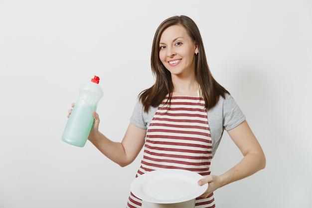 Giovane casalinga in grembiule a strisce isolato. la donna della governante tiene la bottiglia con un liquido più pulito per lavare i piatti, piatto rotondo vuoto bianco