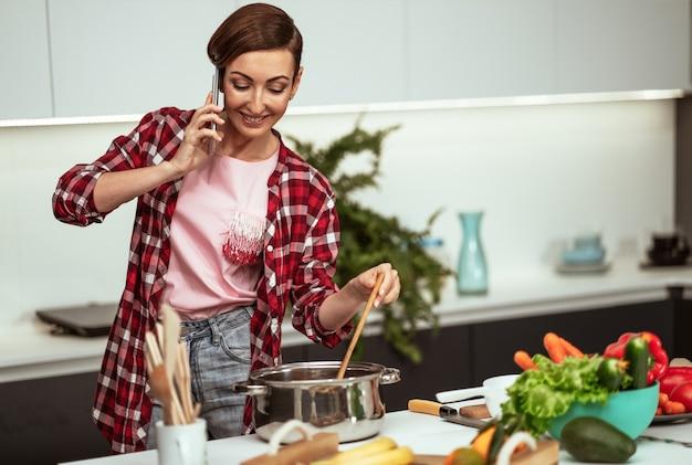 Молодая домохозяйка разговаривает по телефону, замешивая суп на сковороде с короткой прической, пока