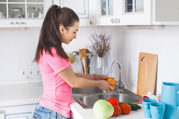 新鮮な野菜を洗う若い主婦
