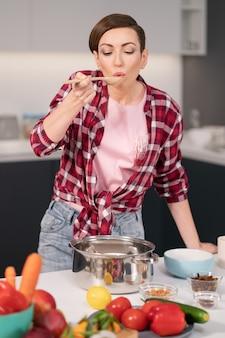 Молодая домохозяйка с короткой прической пробует еду, пока готовит ужин для семьи в
