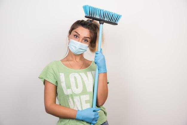 Молодая домохозяйка с лицевой маской, держащей метлу, глядя на выражение лица на белой стене.